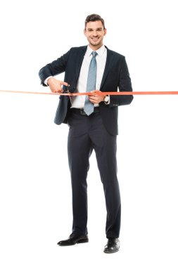 smiling businessman cutting red ribbon with scissors for grand opening, isolated on white