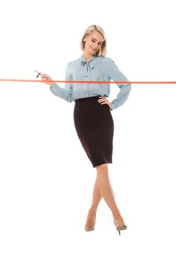 attractive businesswoman standing with scissors near red ceremonial ribbon for grand opening, isolated on white