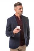 Fotografie Veselý stylový muž v bundě pomocí smartphone izolované na bílém