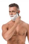 svalnatý shirtless muž s pěnou na holení tváře s břitvou izolované na bílém