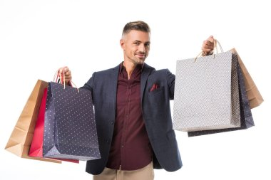 adult male shoppper in jacket showing colorful paper bags isolated on white