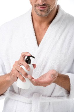 partial view of man in bathrobe using body lotion isolated on white