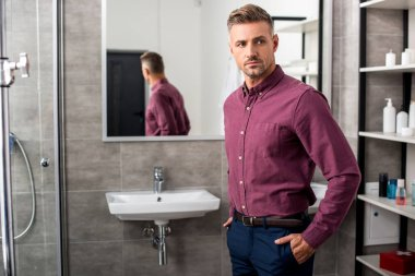 confident adult businessman posing in bathroom at home