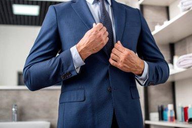 Cropped shot of businessman adjusting suit jacket in bathroom stock vector