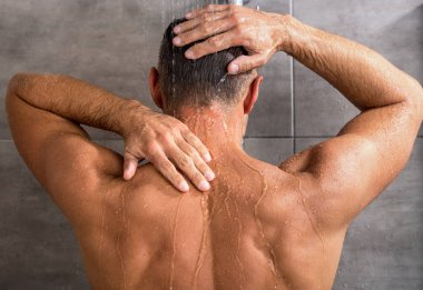 back view of man taking shower in morning at home