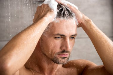 close up portrait of adult man washing hair with shampoo and taking shower