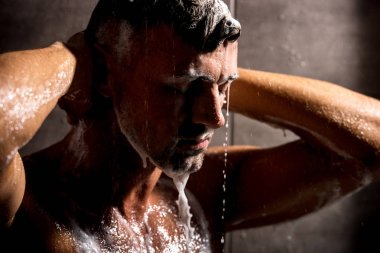 close up view of adult man with closed eyes washing foam in shower