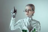 futuristické stříbrné cyborg pokynul rukou a při pohledu od izolované na grey, budoucí technologický koncept