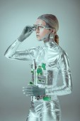 Fotografia futuristica del cyborg argento regolazione protesi dellocchio e guardando lontano isolato su grigio, concetto di tecnologia del futuro