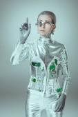 mladá žena robot ukázal rukou na šedé, budoucí technologický koncept