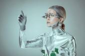 futuristické stříbrný robot pokynul rukou a při pohledu od izolované na grey, budoucí technologický koncept