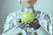 close-up partial view of cyborg holding green apple isolated on grey, future technology concept