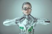 mladá žena robot dotýkat krku a při pohledu na fotoaparát izolované na šedé, budoucí technologický koncept