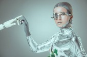 Cyborg dotýká robotické rameno a při pohledu na fotoaparát izolované na šedé, budoucí technologický koncept