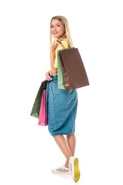 beautiful young woman holding shopping bags and smiling at camera isolated on white