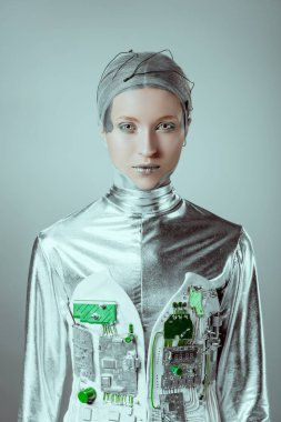 futuristic silver female cyborg looking at camera isolated on grey, future technology concept