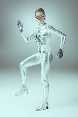 full length view of futuristic cyborg walking and looking at camera on grey, future technology concept