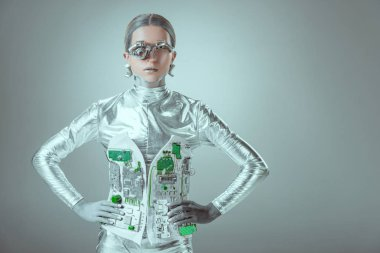futuristic silver cyborg standing with hands on waist and looking at camera isolated on grey, future technology concept