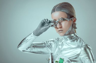 futuristic silver cyborg adjusting eye prosthesis and looking at camera isolated on grey, future technology concept