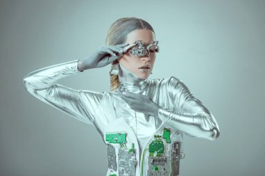 young woman robot posing isolated on grey, future technology concept