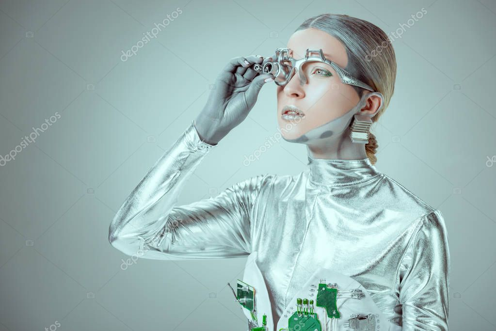 Futuristic silver robot adjusting eye prosthesis and looking away isolated on grey, future technology concept stock vector