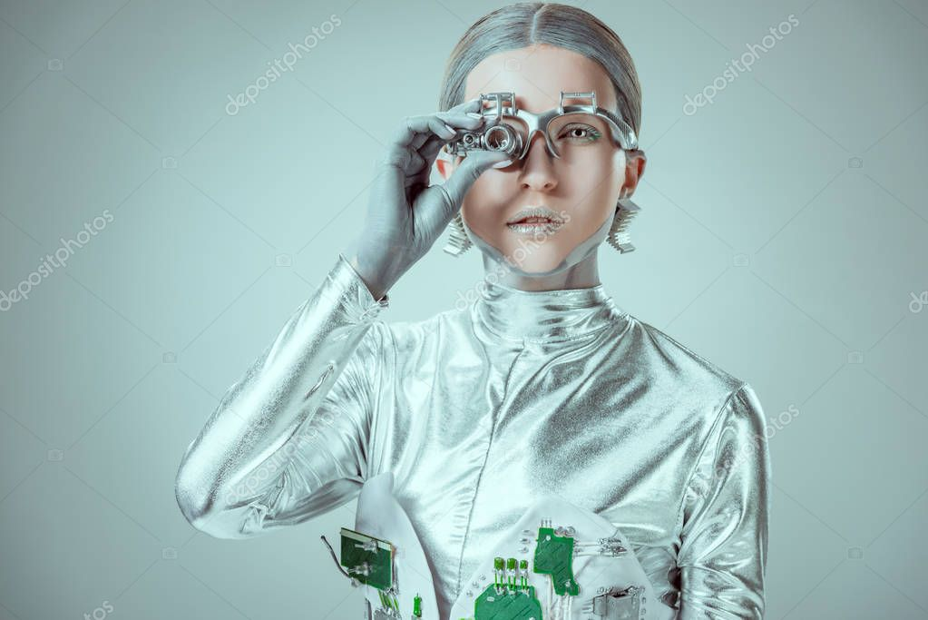 Futuristic silver robot adjusting eye prosthesis and looking at camera isolated on grey, future technology concept stock vector