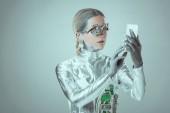 Fotografie stříbrný cyborg pomocí smartphone izolované na šedé, budoucí technologický koncept
