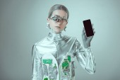 robot che tiene smartphone con lo schermo in bianco e che guarda lobbiettivo isolato il concetto di tecnologia futura, grigio