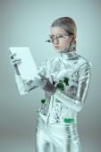 stříbrný robot s oční protézy při pohledu na tabletu izolované na šedé, budoucí technologický koncept