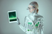 Photo silver robot looking at tablet with chart appliance isolated on grey, future technology concept