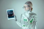 Fotografie Při pohledu na tabletu se rezervace zařízení na šedé, budoucí technologický koncept, samostatný stříbrný robot