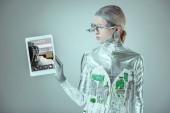 Fényképek ezüst robot látszó-on tabletta-jegyet a készülék elszigetelt szürke, jövőbeni technológia koncepció