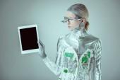 Fotografie stříbrný robot hospodářství tablet s prázdnou obrazovkou izolované na šedé, budoucí technologický koncept