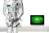 oříznutý obrázek robota sedí na stole u notebooku s obchodní zařízení izolované na bílém, budoucí technologický koncept