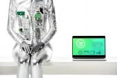 Fényképek körülvágott kép robot ül az asztal mellett laptop vásárlás készülék elszigetelt fehér, jövőbeni technológia koncepció