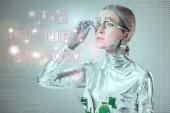 Fotografia futuristica del cyborg argento regolazione protesi dellocchio e guardando il futuro è adesso lettering isolato su grigio con dati digitali, concetto di tecnologia del futuro