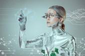 futuristické stříbrné cyborg pokynul rukou a při pohledu na digitální data izolována na šedé, budoucí technologický koncept