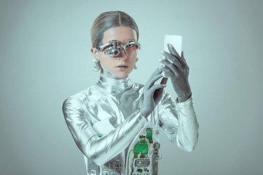 """Картина, постер, плакат, фотообои """"Молодая женщина робота с помощью смартфона, изолированные на концепции серый, будущие технологии"""", артикул 227000032"""