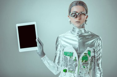 silver robot holding tablet with blank screen and looking at camera isolated on grey, future technology concept