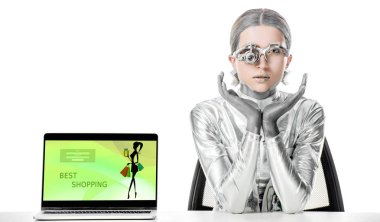 silver robot sitting at table near laptop with best shopping appliance isolated on white, future technology concept