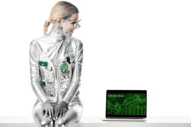 smiling silver robot sitting on table and looking at laptop with online trade appliance isolated on white, future technology concept