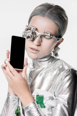 silver robot holding smartphone with blank screen isolated on white, future technology concept