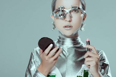 silver robot holding mirror and lipstick isolated on grey, future technology concept
