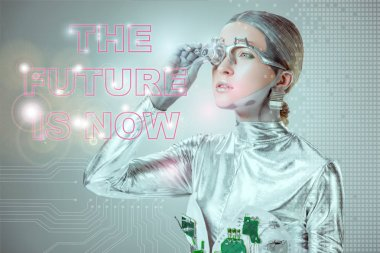 futuristic silver cyborg adjusting eye prosthesis and looking at