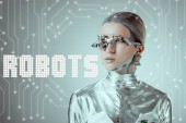 Fotografie futuristic silver cyborg looking away isolated on grey with robots lettering and digital data