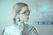 futuristica del cyborg argento con protesi dellocchio guardando i dati digitali su grigio con la scritta intelligenza artificiale