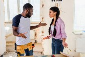 Fotografie side view of irritated woman talking to boyfriend doing shrug gesture during renovation at home