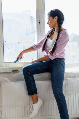 Beautiful young woman mixing paint for wall while sitting on windowsill during renovation of home stock vector
