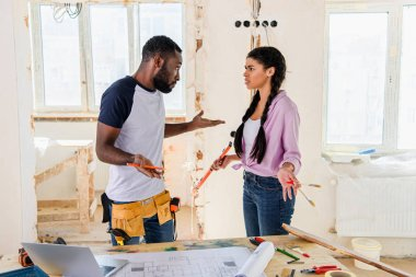 young african american couple having quarrel while making renovation of home