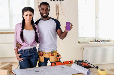 couple holding smartphone with instagram app on screen during renovation